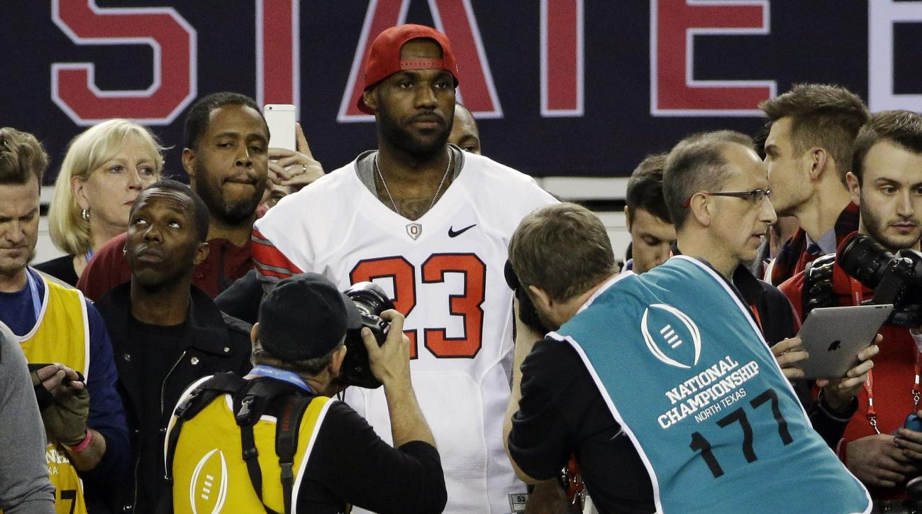 FILE - In a Jan. 12, 2015 file photo, NBA basketball player LeBron James stands on the sideline during the second half of the NCAA college football playoff championship between Ohio State and Oregon game, in Arlington, Texas. Ohio State won 42-20. James a