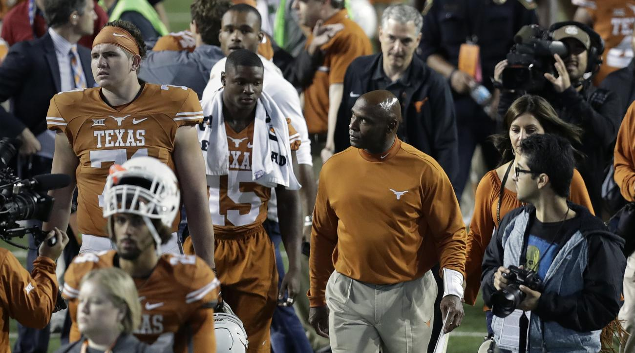 Texas head coach Charlie Strong, center, looks to the stands as he walks off the field with his team following an NCAA college football game against TCU, Friday, Nov. 25, 2016, in Austin, Texas. TCU won 31-9. (AP Photo/Eric Gay)