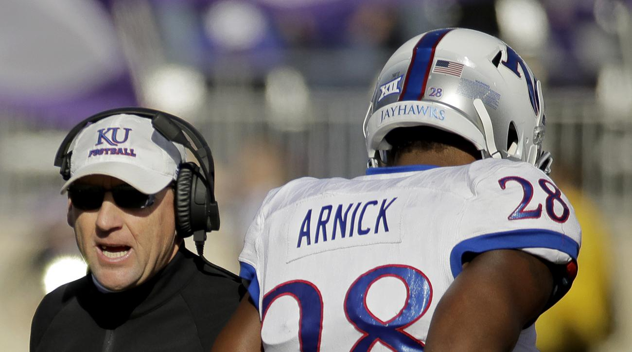 Kansas head coach David Beaty talks to his players during the first half of an NCAA college football game against Kansas State, Saturday, Nov. 26, 2016, in Manhattan, Kan. (AP Photo/Charlie Riedel)