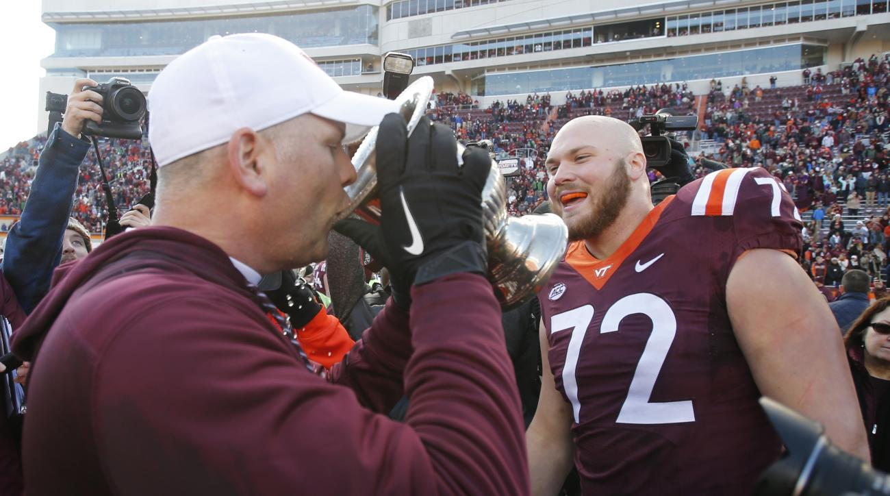 Virginia Tech head coach Justin Fuente drinks from the Commonwealth Cup as he celebrates their 52-10 win over Virginia after an NCAA college football game in Blacksburg, Va., Saturday, Nov. 26, 2016. (AP Photo/Steve Helber)