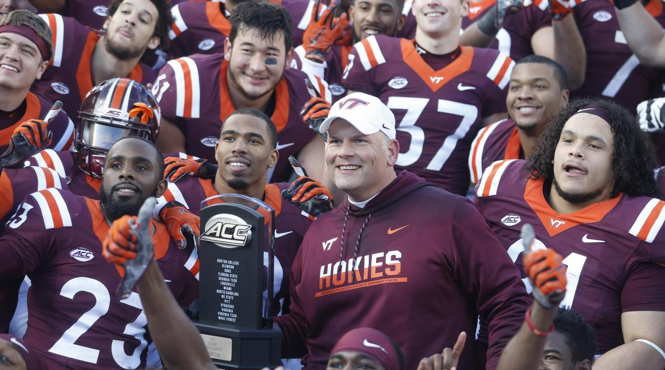 Virginia Tech head coach Justin Fuente and his team celebrate their 52-10 win over Virginia after an NCAA college football game in Blacksburg, Va., Saturday, Nov. 26, 2016. (AP Photo/Steve Helber)
