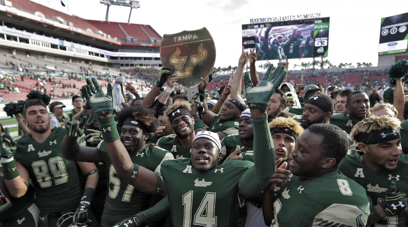 "South Florida players celebrate with the ""War on I-4"" trophy after defeating Central Florida 48-31 in an NCAA college football game Saturday, Nov. 26, 2016, in Tampa, Fla. (AP Photo/Chris O'Meara)"