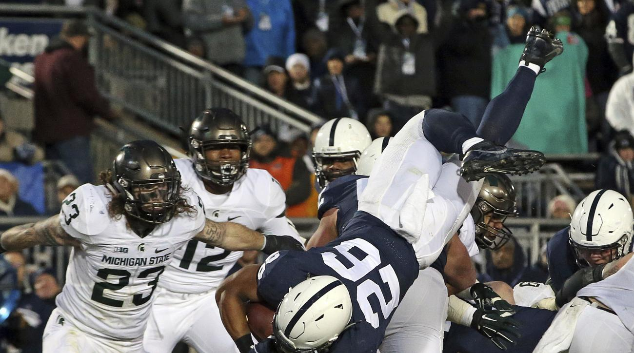 Penn State's Saquon Barkley (26) dives over the pile for a touchdown against Michigan State during the first half of an NCAA college football game in State College, Pa., Saturday Nov. 26, 2016. (AP Photo/Chris Knight)