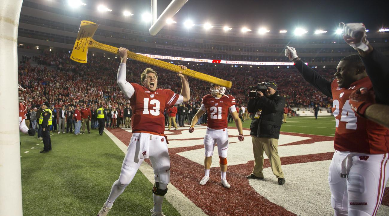 Wisconsin quarterback Bart Houston (13) celebrates with the Paul Bunyan Ax after Wisconsin beat Minnesota 31-17 in an NCAA college football game Saturday, Nov. 26, 2016, in Madison, Wis. (AP Photo/Andy Manis)