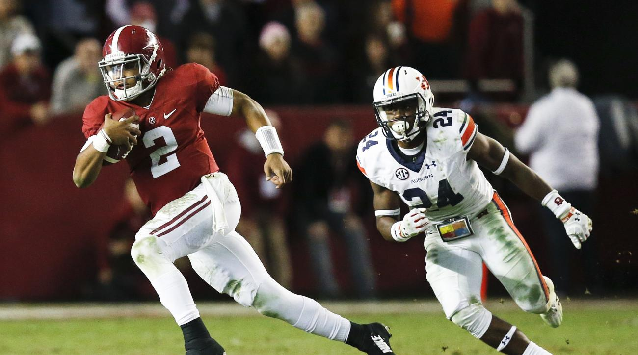 Alabama quarterback Jalen Hurts runs the ball against Auburn defensive back Daniel Thomas during the second half of the Iron Bowl NCAA college football game, Saturday, Nov. 26, 2016, in Tuscaloosa, Ala. Alabama won 30-12. (AP Photo/Brynn Anderson)