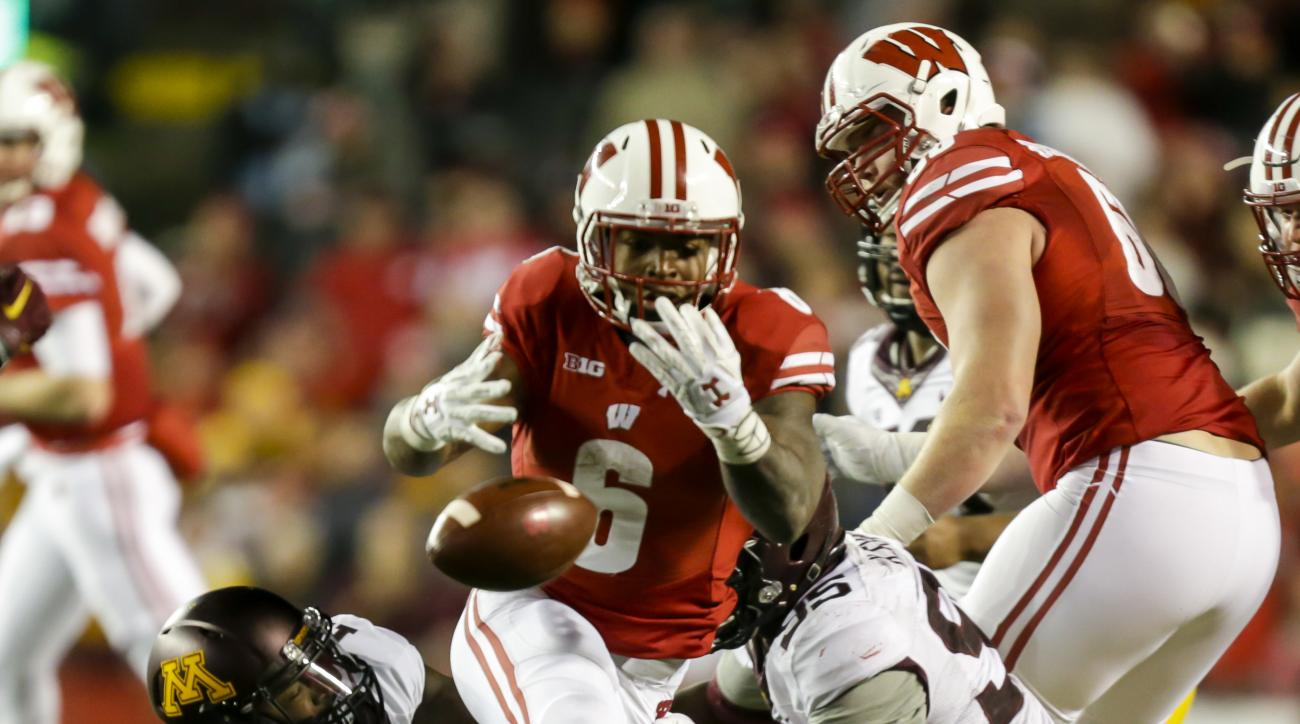 Wisconsin running back Corey Clement (6) fumbles against Minnesota linebacker Jonathan Celestin (13) and defensive lineman Hendrick Ekpe during the second half of an NCAA college football game Saturday, Nov. 26, 2016, in Madison, Wis. Wisconsin won 31-17.