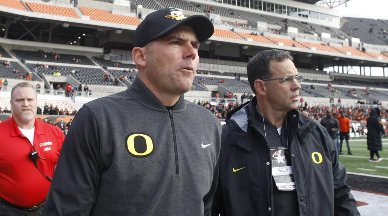 Oregon head coach Mark Helfrich, center, comes onto the field for an interview before an NCAA college football game against Oregon State, in Corvallis, Ore., Saturday Nov. 26, 2016. (AP Photo/Timothy J. Gonzalez)