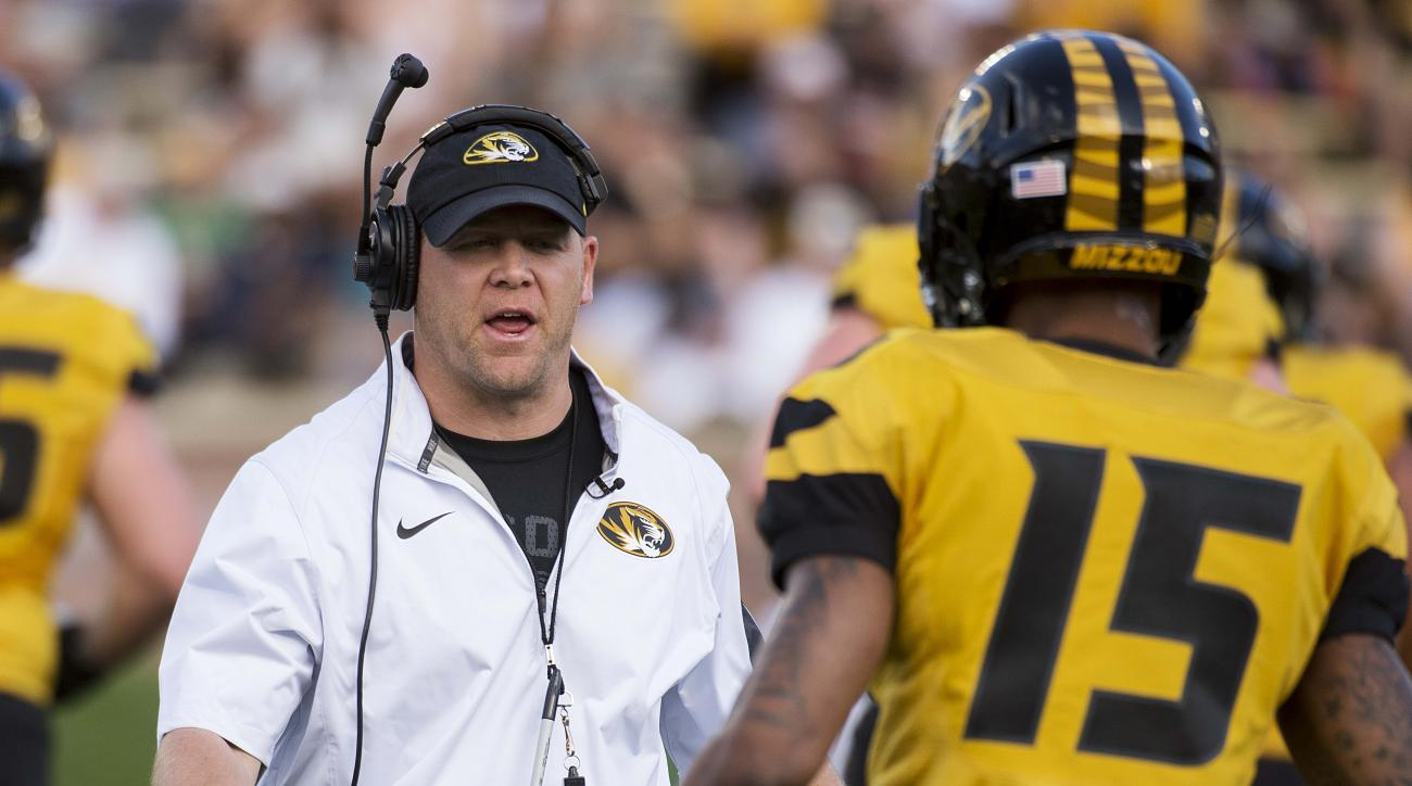 FILE - In this Saturday, April 16, 2016 file photo, Missouri head coach Barry Odom, left, talks to player Keyon Dilosa, right, during a spring NCAA college football game in Columbia, Mo. (AP Photo/L.G. Patterson, File)