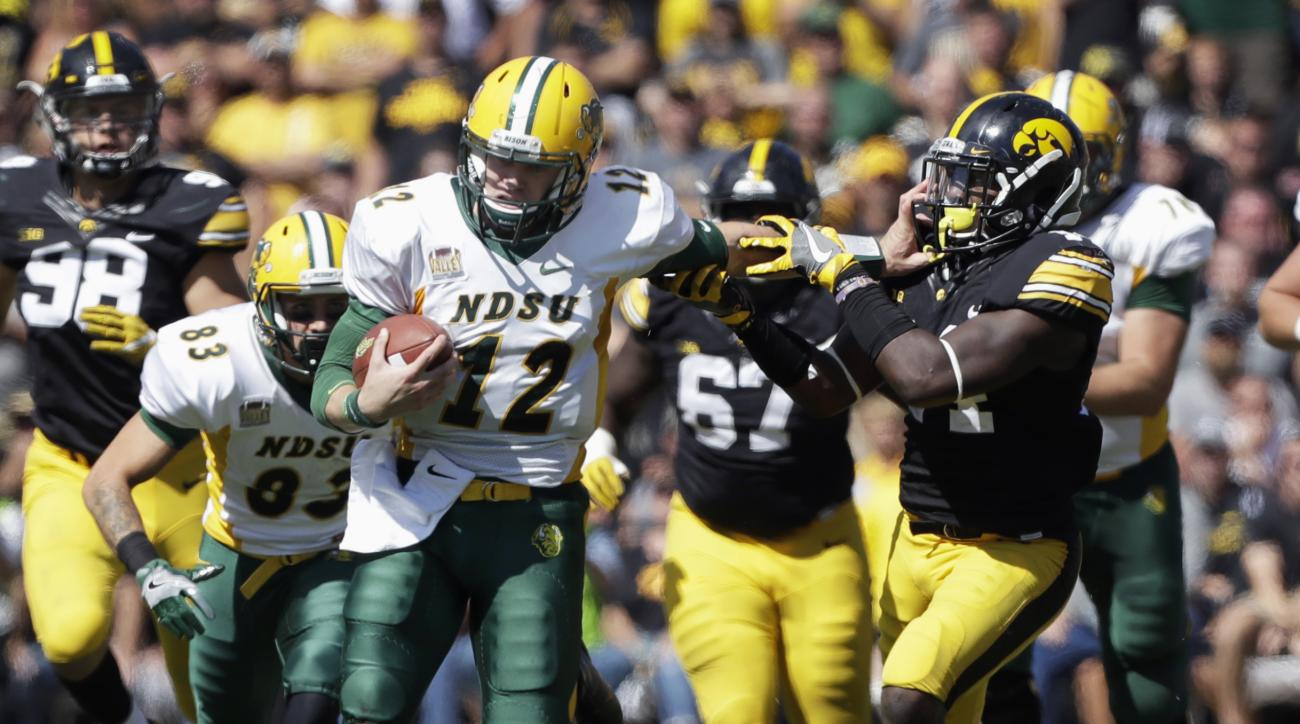 FILE - In this Sept. 17, 2016, file photo, North Dakota State quarterback Easton Stick (12) tries to break a tackle by Iowa's Desmond King during an NCAA college football game in Iowa City, Iowa. North Dakota State won 23-21. North Dakota State faces San