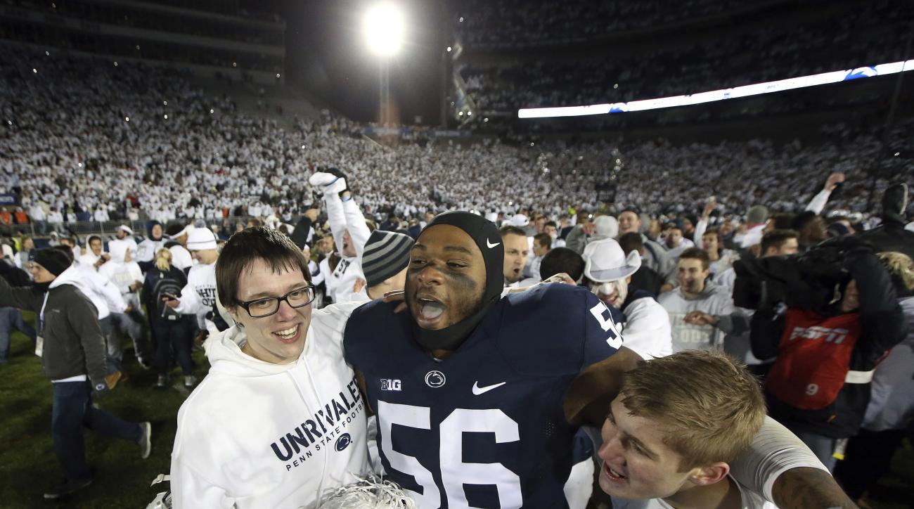 FILE - In this Oct. 22, 2016, file photo, Penn State's Tyrell Chavis (56) celebrates with fans as they rush the field after Penn State upset Ohio State in an NCAA college football game in State College, Pa. A blocked field goal in the fourth quarter again
