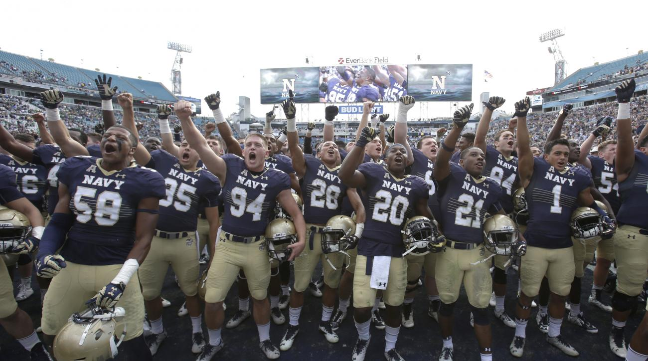 FILE - In this Nov. 5, 2016, file photo, Navy players celebrate after defeating Notre Dame 28-27 in an NCAA college football game Saturday, Nov. 5, 2016, in Jacksonville, Fla. If Navy is in position to earn a spot in a major bowl game when the rankings an