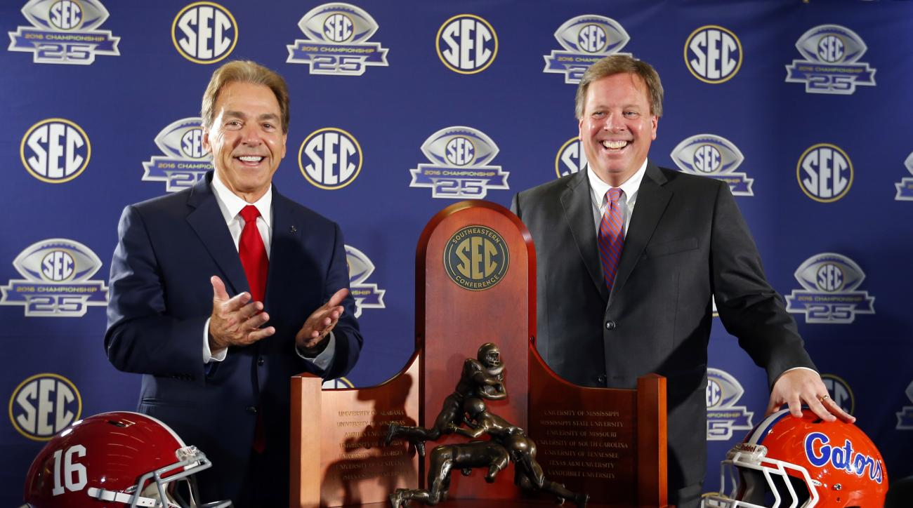 Alabama head coach Nick Saban, left, and Florida head coach Jim McElwain pose for a photo with the trophy at the press conference for the Southeastern Conference Championship NCAA college football game, Friday, Dec. 2, 2016, in Atlanta. (AP Photo/Butch Di