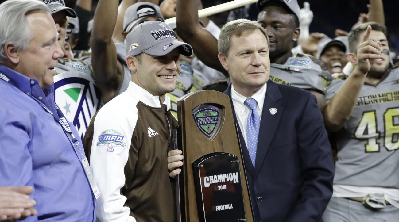 Western Michigan head coach P.J. Fleck is presented the Mid-American Conference championship trophy by Commissioner Dr. Jon Steinbrecher after an NCAA college football game against Ohio, Friday, Dec. 2, 2016, in Detroit. (AP Photo/Carlos Osorio)