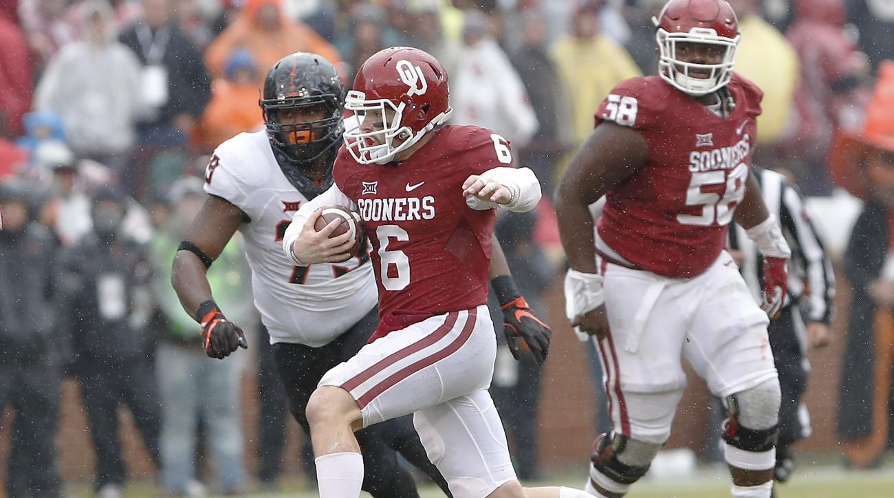 Oklahoma quarterback Baker Mayfield (6) runs in front of Oklahoma State defensive tackle Darrion Daniels (79) during the second half of an NCAA college football game, Saturday, Dec. 3, 2016, in Norman, Okla. Oklahoma won 38-20. (AP Photo/Alonzo Adams)
