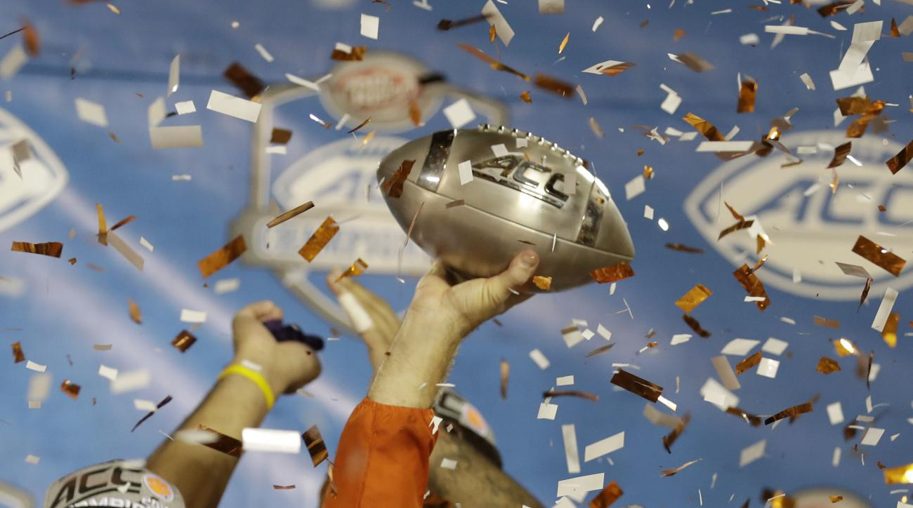 Clemson head coach Dabo Swinney raises the Atlantic Coast Conference championship NCAA college football trophy, Sunday, Dec. 4, 2016, in Orlando, Fla. Clemson defeated Virginia Tech 42-35. (AP Photo/Chris O' Meara)