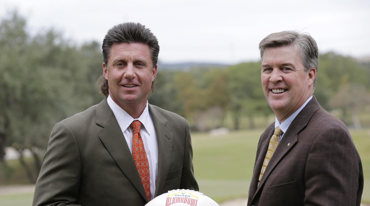 Oklahoma State head coach Mike Gundy, left, and Colorado head coach Mike MacIntyre, right, pose for photos following a news conference, Thursday, Dec. 8, 2016, in San Antonio. Oklahoma State and Colorado will play in the Alamo Bowl on Dec. 29. (AP Photo/E