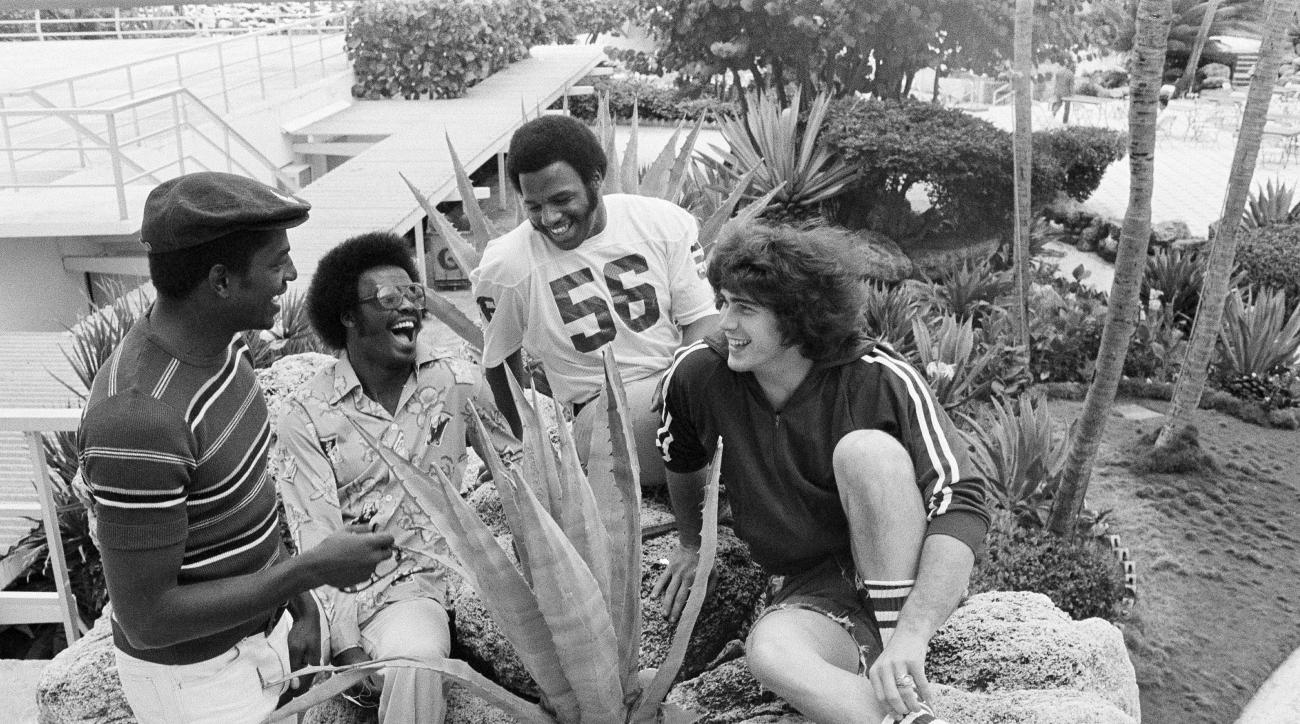 "FILE - In this Dec. 29, 1975, file photo, members of the Oklahoma Sooners college football team relax in the garden of their hotel in Miami Beach, Fla. From left are Victor Brown, Mike Phillips, Glenn Comeaux and James ""Jimbo"" Elrod. The Oklahoma Highway"
