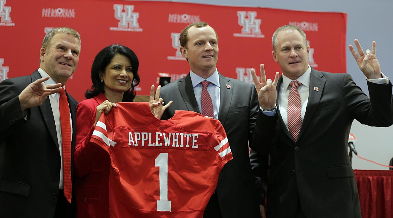 University of Houston Board of Regent Chairman Tillman Fertitta, left, school President Renu Khator, second from left, and Vice President of Athletics Hunter Yurachek, right, gesture during a press conference to introduce new NCAA college football coach M