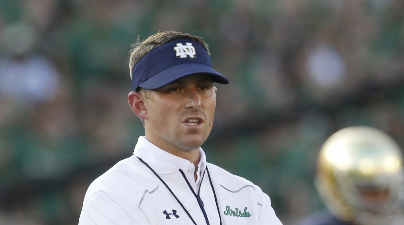 FILE- In this Sept. 5, 2015, file photo, Notre Dame offensive coordinator/quarterbacks coach Mike Sanford watches his team before an NCAA college football game against Texas in South Bend, Ind. Sanford's star began rising during two stints at Stanford, un