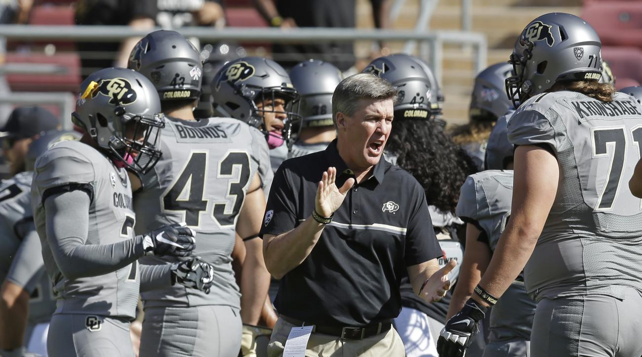 FILE - In this Oct. 22, 2016, file photo, Colorado coach Mike MacIntyre, center, leads his team in warm up exercises before an NCAA college football game against Stanford, in Stanford, Calif. The Associated Press has been selecting a college football coac