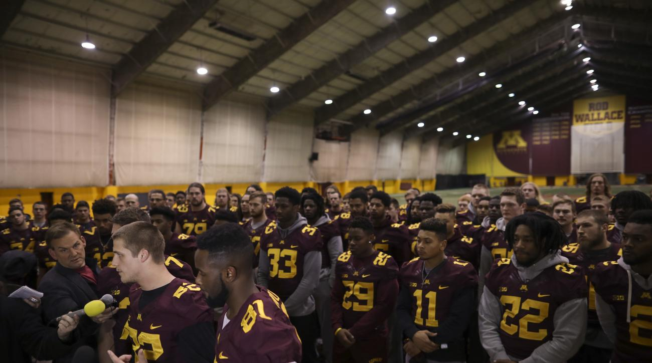 University of Minnesota wide receiver Drew Wolitarsky, flanked by quarterback Mitch Leidner, obscured behind Wolitarsky, and tight end Duke Anyanwu gestures as he stands in front of other team members while talking to reporters in the Nagurski Football Co
