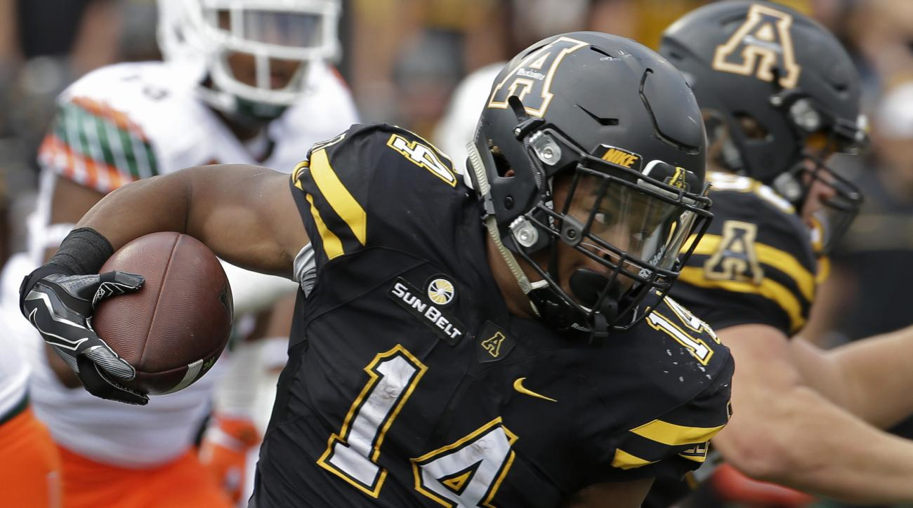 FILE - In this Sept. 17, 2016, file photo, Appalachian State's Marcus Cox (14) runs past Miami's Trent Harris (33) during the first half of an NCAA college football game, in Boone, N.C. Appalachian State and Toledo have matching 9-3 records, running backs
