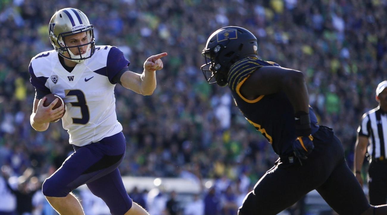 In this Oct. 8, 2016, photo, Washington quarterback Jake Browning (3) points to Oregon's Jimmie Swain (18) while rushing for a touchdown in the first quarter of an NCAA college football game in Eugene, Ore. It was so out of character it became the definin