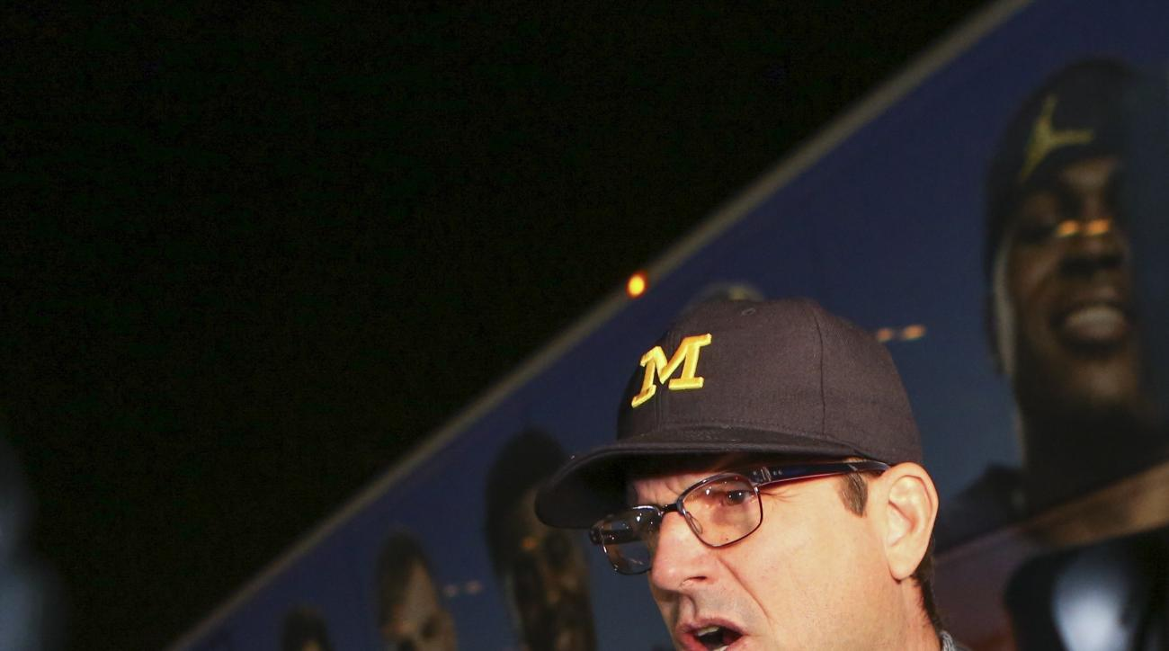 Michigan's head coach Jim Harbaugh talks to the press he and his team arrived to the Miami International Airport on Sunday, Dec. 25, 2016. Michigan will face-off against Florida State on Friday in the Orange Bowl NCAA college football game. (Matias J. Ocn