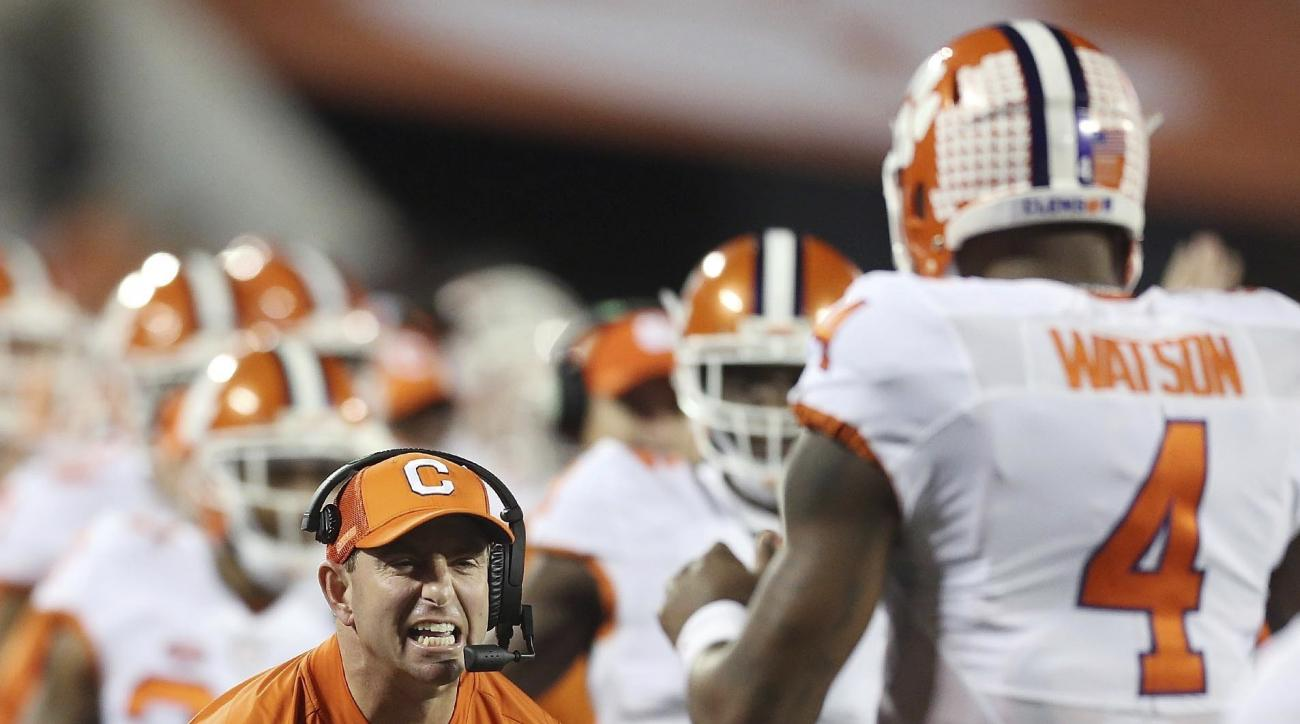FILE - In this Dec. 3, 2016, file photo, Clemson coach Dabo Swinney yells in celebration to quarterback Deshaun Watson (4) after a touchdown against Virginia Tech during the Atlantic Coast Conference championship football game in Orlando, Fla. The Tigers