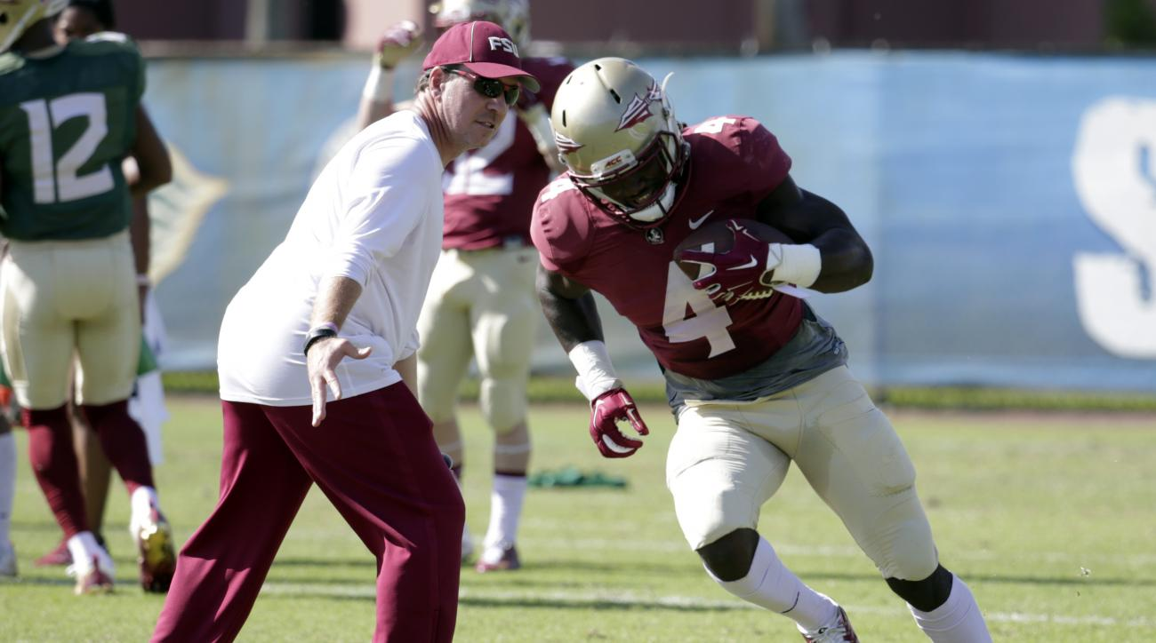 Florida State running back Dalvin Cook (4) runs as head coach Jimbo Fisher, left, looks on during NCAA college football practice, Tuesday, Dec. 27, 2016, in Fort Lauderdale, Fla. Florida State plays Michigan in the Orange Bowl Friday. (AP Photo/Lynne Slad
