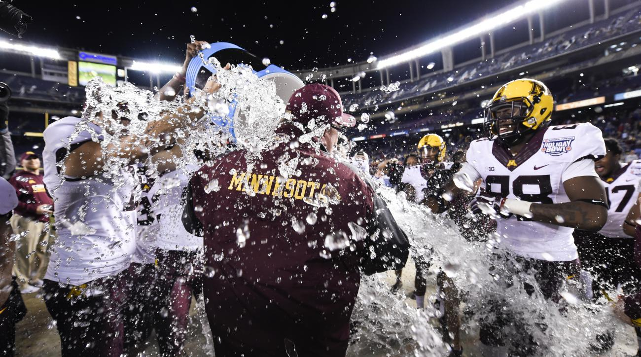 Minnesota head coach Tracey Claeys has a cooler of Gatorade dumped over him after Minnesota defeated Washington State 17-12 in the Holiday Bowl NCAA college football game, Tuesday, Dec. 27, 2016, in San Diego. (AP Photo/Denis Poroy)