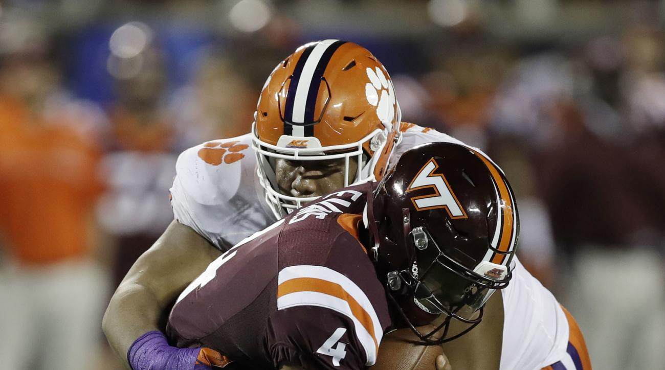 FILE - In a Saturday, Dec. 3, 2016 file photo, Clemson defensive tackle Dexter Lawrence (90) sacks Virginia Tech quarterback Jerod Evans (4), during the second half of the Atlantic Coast Conference championship NCAA college football game, in Orlando, Fla.