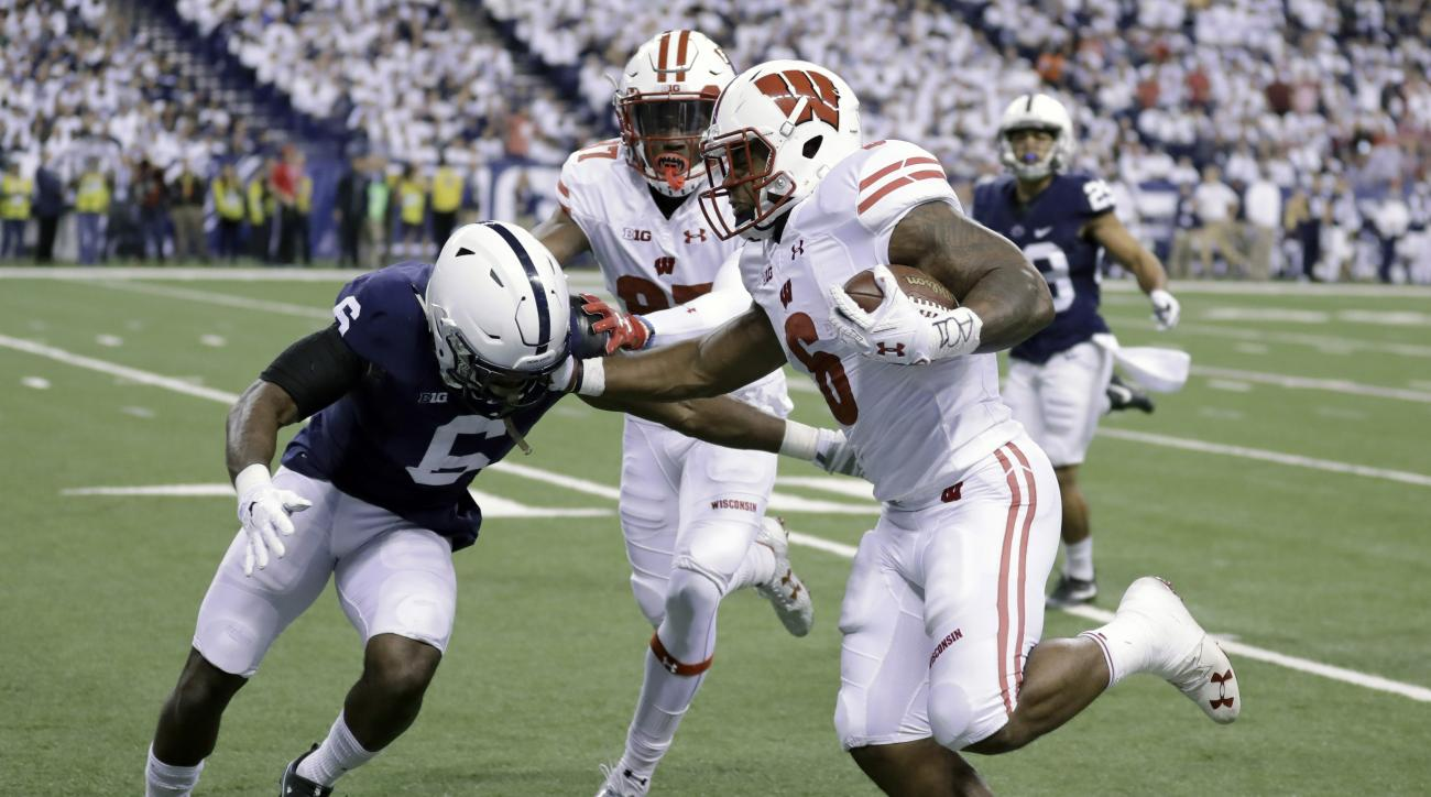 FILE - In a Saturday, Dec. 3, 2016 file photo, Wisconsin's Corey Clement, right, runs with the ball past Penn State's Malik Golden, left, for a 67-yard touchdown during the first half of the Big Ten championship NCAA college football game, in Indianapolis