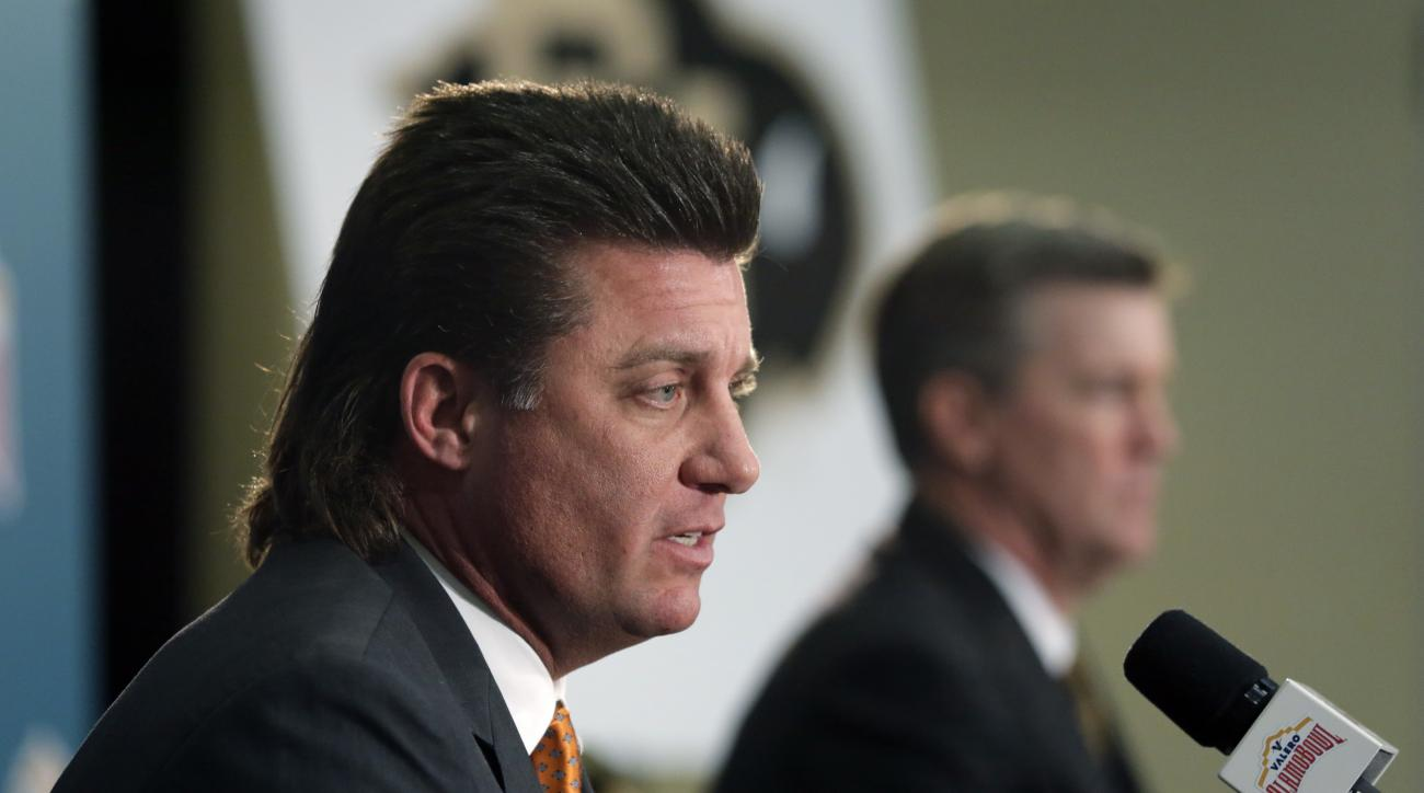 Oklahoma State head coach Mike Gundy, left, and Colorado head coach Mike MacIntyre, right, take part in a news conference for the Alamo Bowl NCAA college football game, Wednesday, Dec. 28, 2016, in San Antonio. Colorado will face Oklahoma State in the Ala