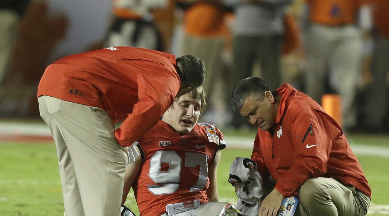 FILE - This Jan. 3, 2014 file photo shows Ohio State defensive lineman Joey Bosa being attended to after a play during the first half of the Orange Bowl NCAA college football game between Clemson and Ohio State in Miami Gardens, Fla. Ohio State's defense