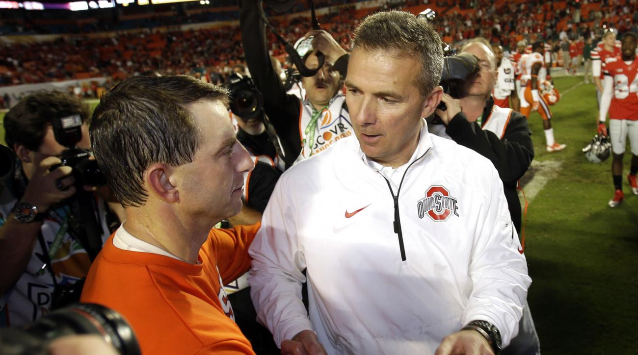 FILE - In this Jan. 4, 2014, file photo, Ohio State head coach Urban Meyer, right, shakes hands with Clemson head coach Dabo Swinney after the Orange Bowl NCAA college football game, Saturday, Jan. 4, 2014, in Miami Gardens, Fla. Clemson defeated Ohio Sta