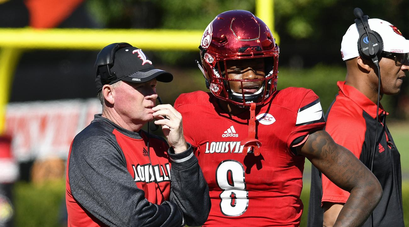 FILE - In this Oct. 22, 2016, file photo, Louisville head coach Bobby Petrino talks with Lamar Jackson (8) during a time out in their NCAA college football game against North Carolina State in Louisville, Ky.  At different points of the season, LSU and Lo