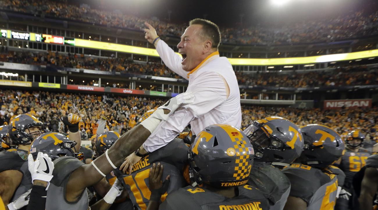 Tennessee head coach Butch Jones is carried by his players after Tennessee beat Nebraska in the Music City Bowl NCAA college football game Friday, Dec. 30, 2016, in Nashville, Tenn. Tennessee won 38-24. (AP Photo/Mark Humphrey)