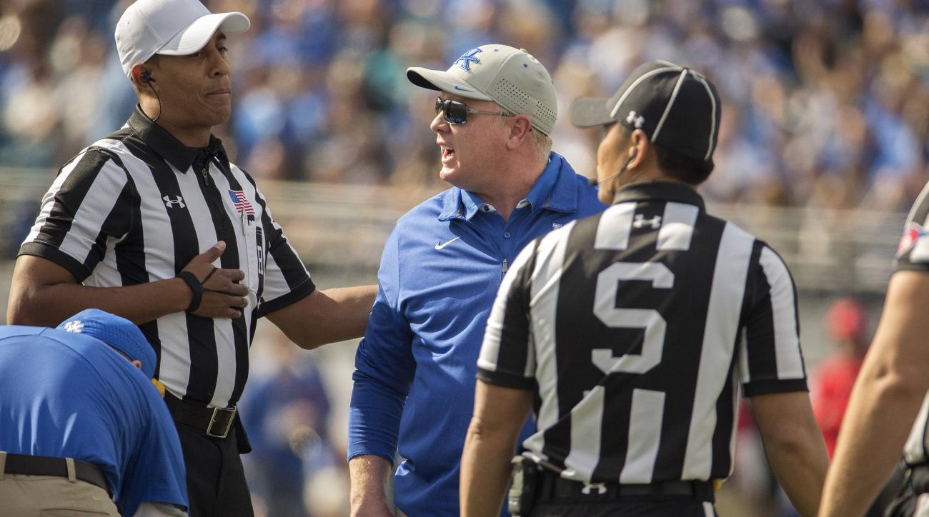 Kentucky head coach Mark Stoops, center, argues with referee Reggie Smith, left, during the first half of the TaxSlayer Bowl NCAA college football game against Georgia Tech, Saturday, Dec. 31, 2016, in Jacksonville, Fla. (AP Photo/Stephen B. Morton)