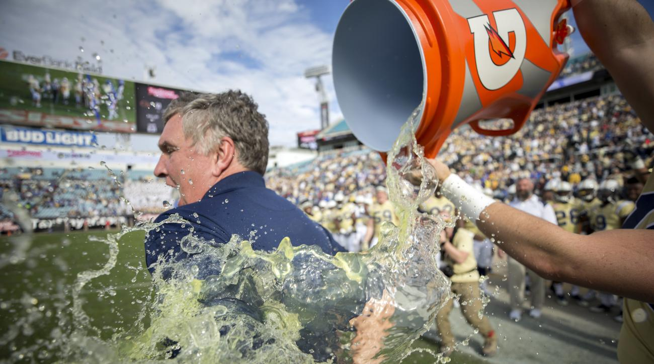 Georgia Tech back up quarterback Matthew Jordan (11) douses Georgia Tech head coach Paul Johnson at the end of the TaxSlayer Bowl NCAA college football game against Kentucky, Saturday, Dec. 31, 2016, in Jacksonville, Fla. Georgia Tech beat Kentucky 33-18.