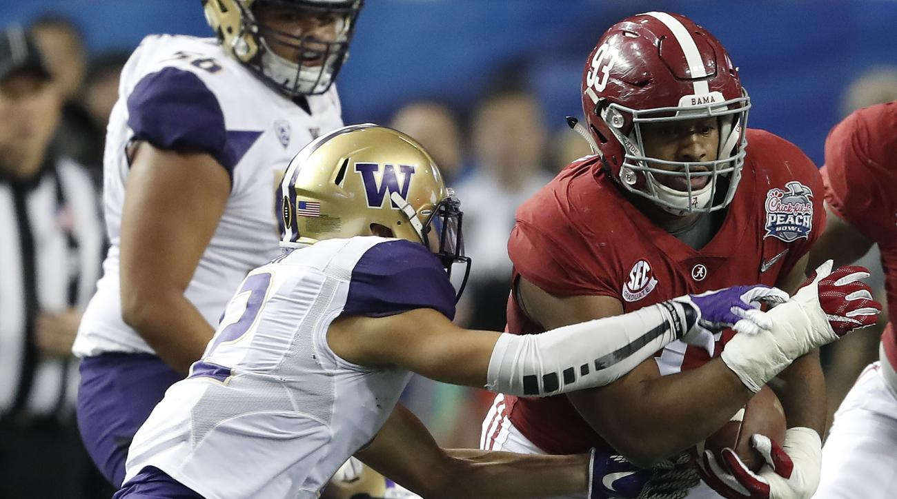 Alabama defensive lineman Jonathan Allen (93) runs after recovering a fumble as Washington wide receiver Aaron Fuller (12) defends during the first half of the Peach Bowl NCAA college football playoff game, Saturday, Dec. 31, 2016, in Atlanta. (AP Photo/J