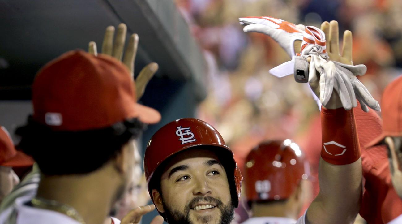 FILE - In this Sept. 22, 2015, file photo, St. Louis Cardinals' Tony Cruz is congratulated by teammates after scoring on a sacrifice fly by Tommy Pham during the seventh inning of a baseball game against the Cincinnati Red, in St. Louis. The Royals have a