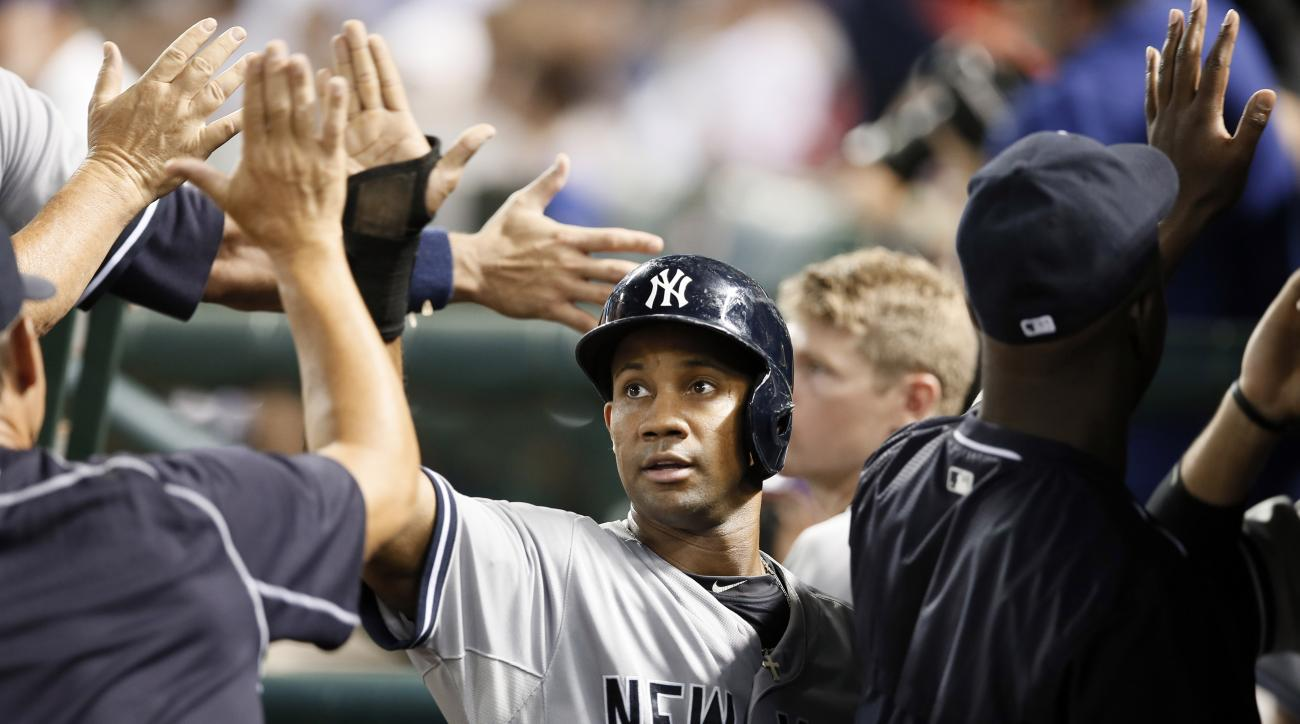 FILE - In this July 28, 2015, file photo, New York Yankees' Chris Young is congratulated in the dugout after he and Garrett Jones scored on a John Ryan Murphy single in the sixth inning of a baseball game against the Texas Rangers, in Arlington, Texas. Ou