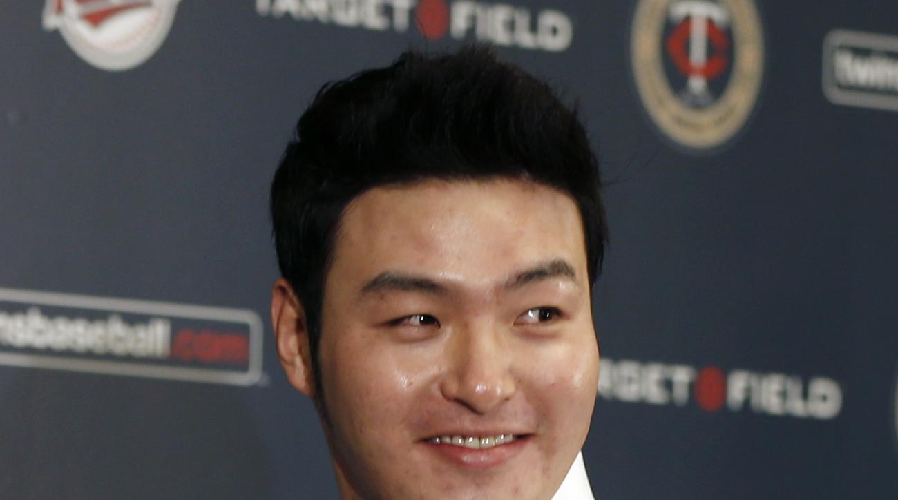 Byung Ho Park of South Korea poses wearing his new jersey as he meets the media, Wednesday, Dec. 2, 2015, in Minneapolis, after signing a three-year contract with the Minnesota Twins baseball team. (AP Photo/Jim Mone)