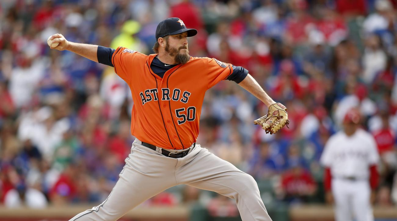 FILE - In this April 10,  2015, file photo, Houston Astros relief pitcher Chad Qualls (50) throws against the Texas Rangers in the eighth inning of a baseball game in Arlington, Texas. The Colorado Rockies tried to fill big holes in their bullpen by agree