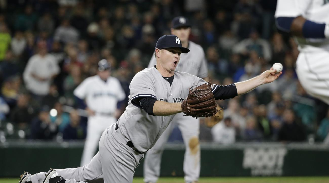 FILE- In this June 2, 2015, file photo, New York Yankees relief pitcher Justin Wilson throws to first to complete a double play against the Seattle Mariners in the 10th inning of a baseball game in Seattle. In a trade was announced on Wednesday, Dec. 9, t
