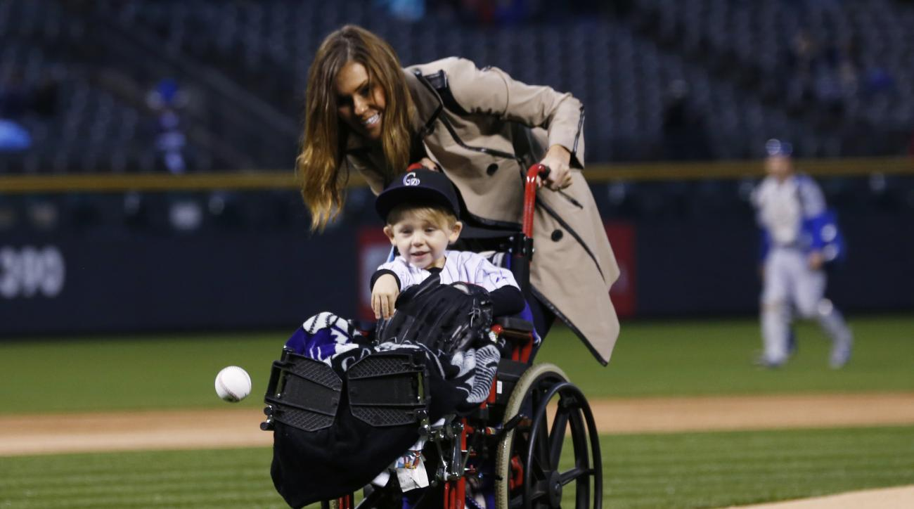 FILE - In this May 8, 2015, file photo, two-year-old Jameson Axford throws out the ceremonial first pitch as his mother, Nicole, looks on before the Colorado Rockies host the Los Angeles Dodgers in a baseball game in Denver. Little Jameson is running arou