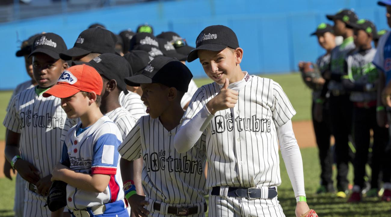 A young baseball player gives a thumbs up before the start of a baseball clinic, lead by MLB players in Havana, Cuba, Wednesday, Dec. 16, 2015. Los Angeles Dodgers outfielder Yasiel Puig, St. Louis Cardinals catcher Brayan Pena and Chicago White Sox first