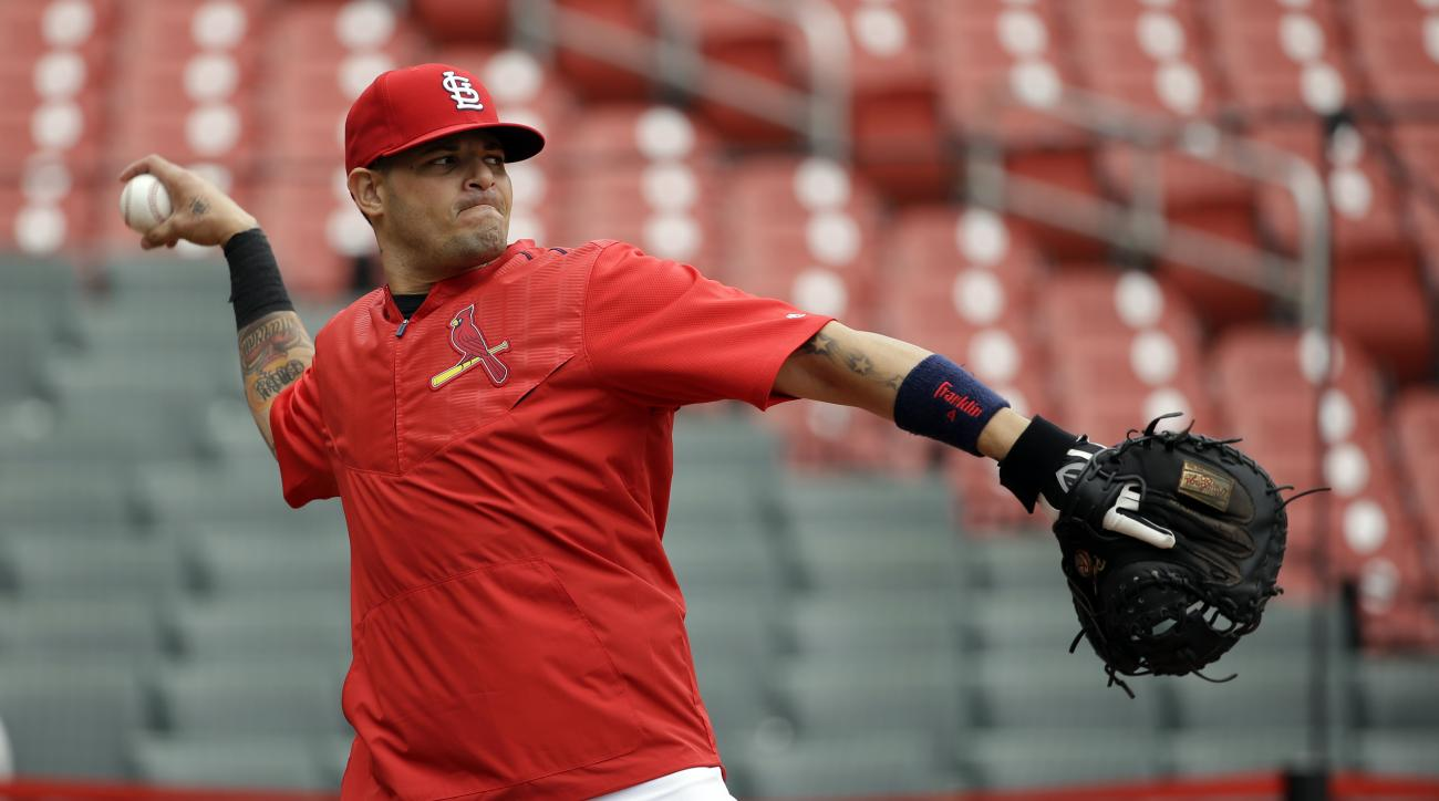 St. Louis Cardinals catcher Yadier Molina throws during baseball practice on Wednesday, Oct. 7, 2015, in St. Louis. Molina has been out since Sept. 20 with a partially torn ligament in his left thumb but expects to play while wearing a splint when the Car