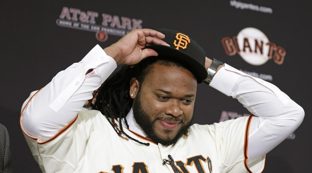 San Francisco Giants pitcher Johnny Cueto puts on a new cap during a media availability Thursday, Dec. 17, 2015, in San Francisco. Cueto was introduced by the Giants a day after passing his physical to complete a $130 million, six-year contract. Cueto, wh